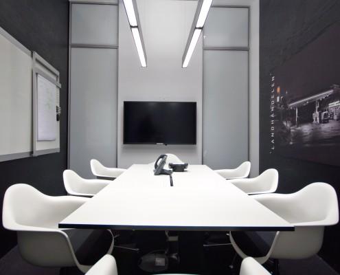 Hvit innredning i kontorbygg med glassdører i bakgrunnen