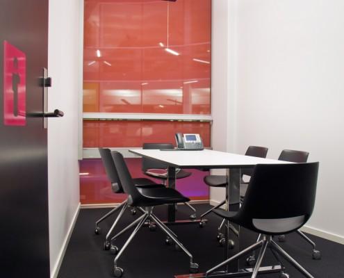 Intimt møterom med rød vegg bak interiørarkitekt Berentsen